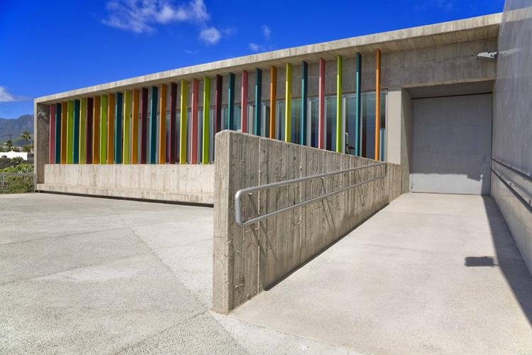 Vista del edificio desde la plaza en la planta superior con detalle de lamas de colores en la fachada