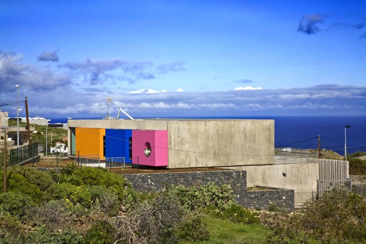Vista de la parte trasera del edificio desde la carretera donde resaltan los cubos de colores sobre el hormigón visto utilizado en el resto del edificio