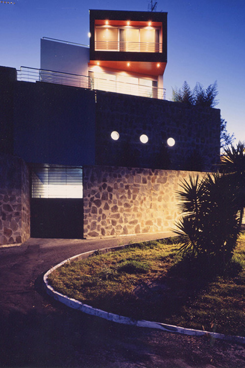 Vista nocturna de la fachada principal de la vivienda desde la calle