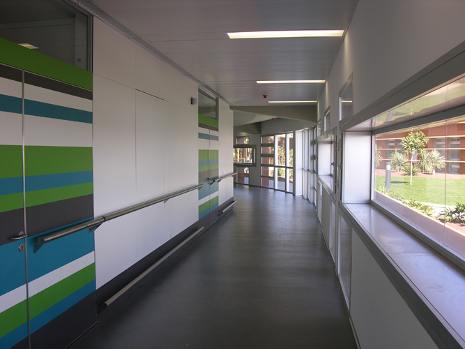 Vista de uno de los pasillos de las habitaciones con código de colores como ayuda al usuario y ventanas hacia los jardines del hospital de Nuestra Señora de los Dolores