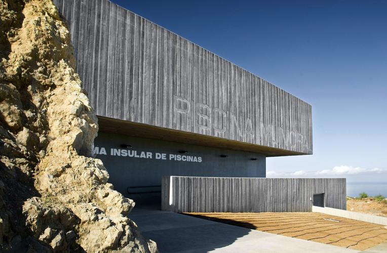 Vista del acceso principal al edificio. El edificio parece que sale de la roca natural existente en el lugar.