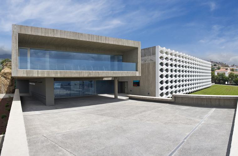 Visión desde la plaza de acceso al edificio, donde se ve la pieza principal con la celosía y la otra pieza de hormigón visto y vidrio
