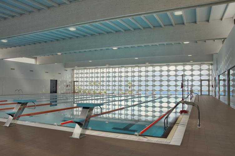 Vista de la piscina desde el interior del edificio, donde se ve reflejado la celosía de la fachada.